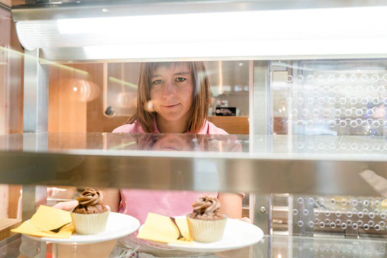 Eine Fraun arrangiert Cupcakes.