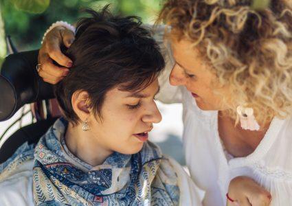 Eine Frau legt ihre Hand hinter den Kopf ihrer Tochter, die im Rollstuhl sitzt