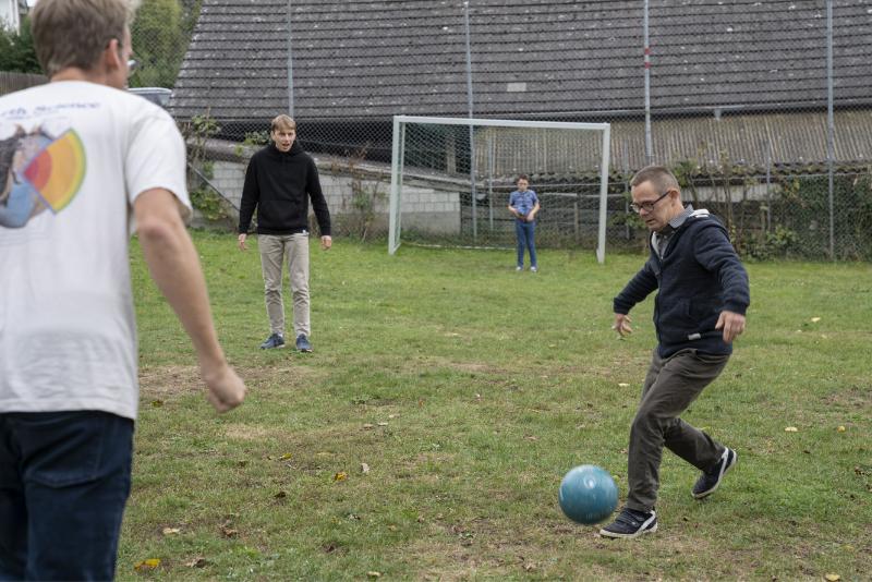 Quatre jeunes hommes sont en train de jouer au football.