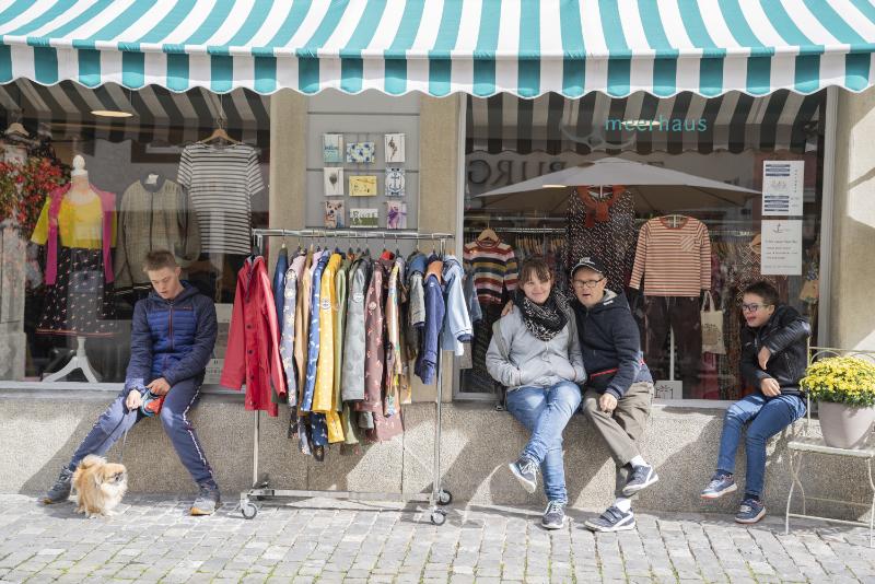 Vier junge Leute sitzen vor einem Schaufenster eines Kleidergeschäfts.