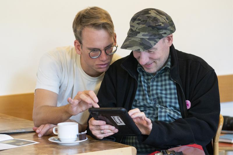Zwei Männer schauen auf ein Tablet.