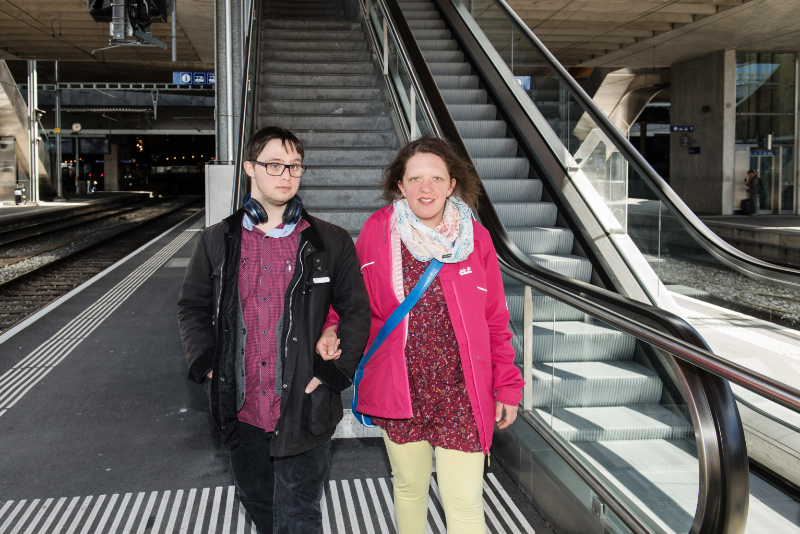 Deux jeunes avec un handicap mental descendent d'un escalator.