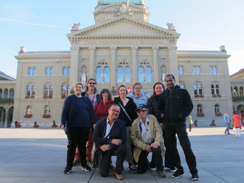 Un groupe d'hommes et de femmes devant le Palais fédéral à Berne.