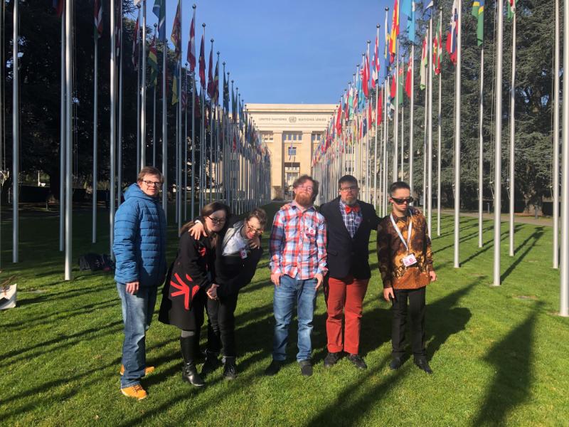 Six jeunes gens se tiennent sur la pelouse, devant le siège des Nations unies à Genève