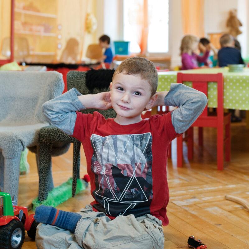 Ein Junge sitzt auf dem Bodern und hat die Hände hinter dem Kopf verschränkt.