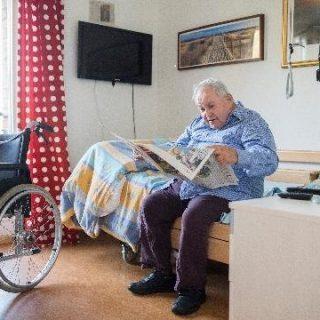 Ein alter Mann sitzt auf seinem Bett und liest die Zeitung
