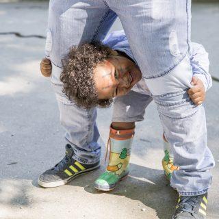 Un enfant sourit en tenant les deux jambes de son père