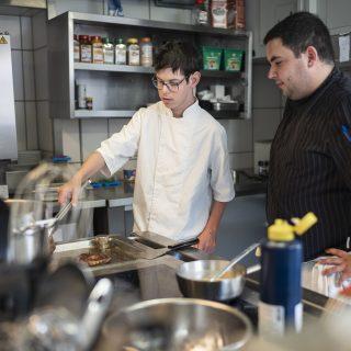 Jonas, à gauche, prépare les commandes qui lui sont confiées, ici avec Remy (chef cuisinier), à droite