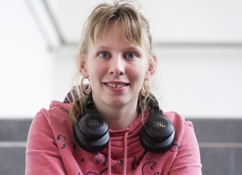 Une jeune femme blonde a des écouteurs sur ses épaules.