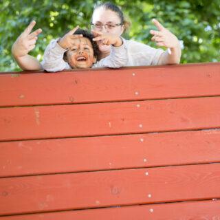 Une photo d'une mère et sa fille qui jouent derrière un balustrade