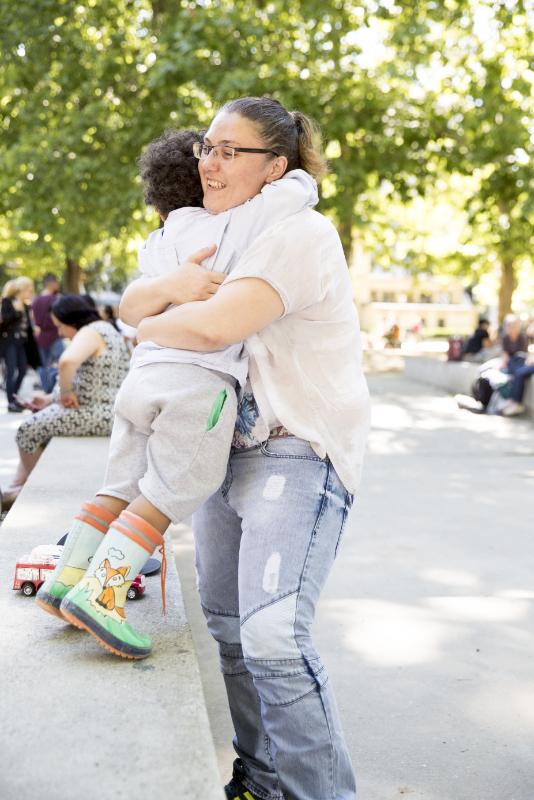 Une jeune femme en jeans étreint son petit garçon.