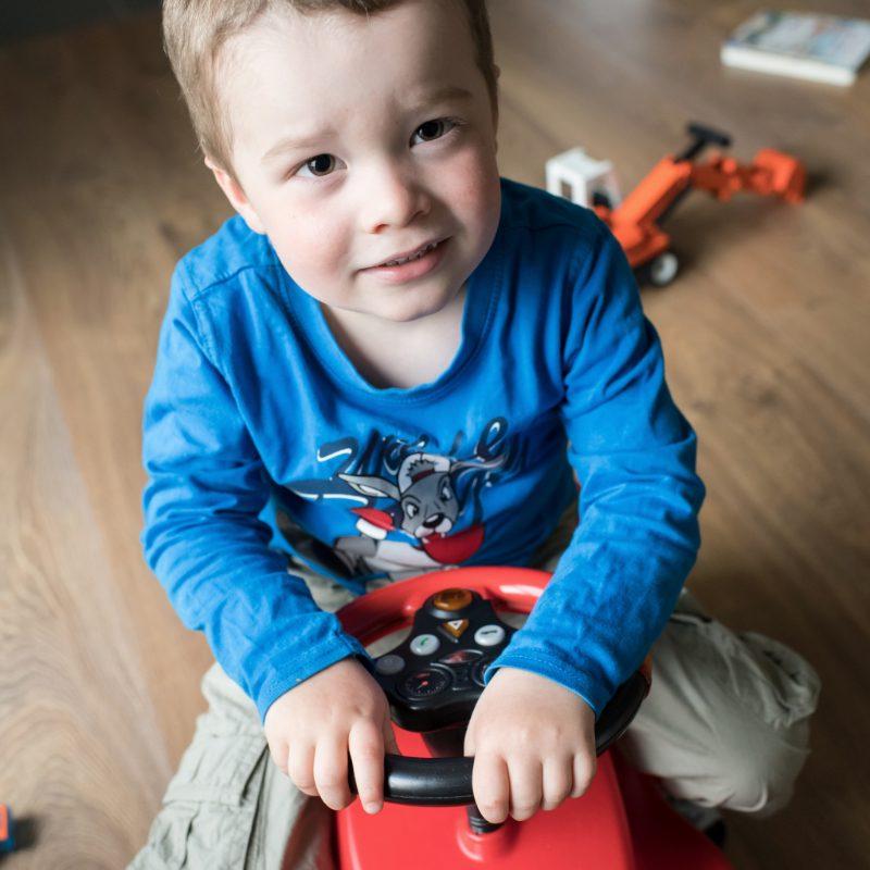 Un garçon en pull bleu est assis sur un petit tracteur rouge.