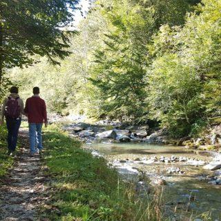 Zwei Personen gehen auf einem Weg einem Fluss entlang.