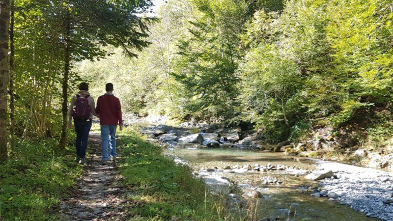 Deux personnes marchent côte à côte le long d'une rivière.