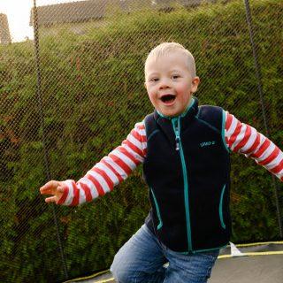 Ein Junge mit Trisomie 21 schaut ins Objektiv.