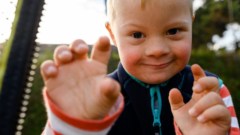 Un jeune garçon vivant avec une trisomie 21 regarde l'objectif en grimaçant.