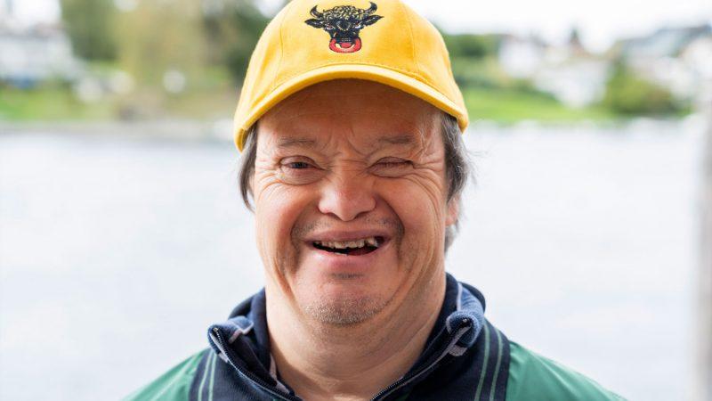 Ein Mann mit Trisomie 21 lächelt ins Objektiv.