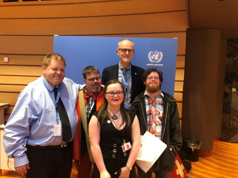 Une femme et quatre hommes se trouvent dans le bâtiment de l'ONU à Genève.