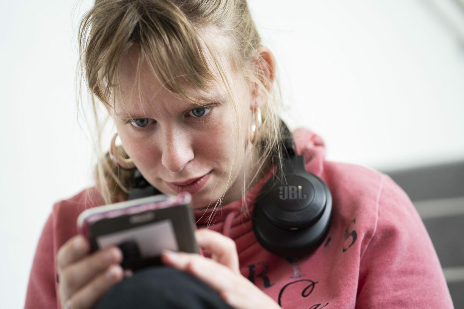 Eine junge Frau schaut auf ihr Handy
