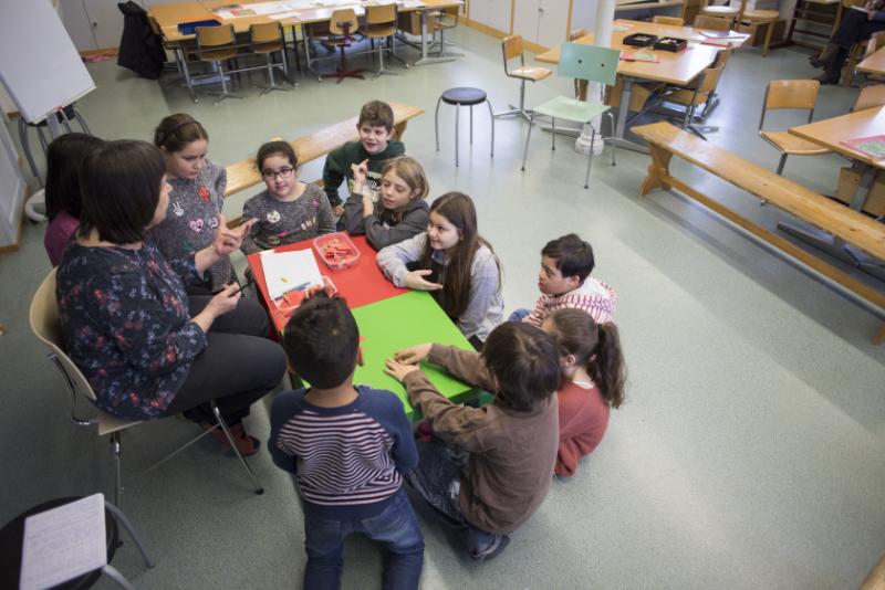 Eine Frau und eine Gruppe von Schüler*innen sitzen um einen Tisch herum.