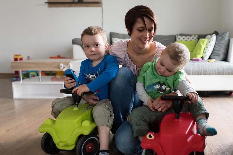 Eine Frau kniet zwischen zwei kleinen Buben, die auf Spielzeugautos sitzen.