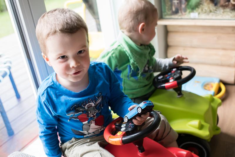 Zwei kleine Buben sitzen auf ihren Spielzeugautos.