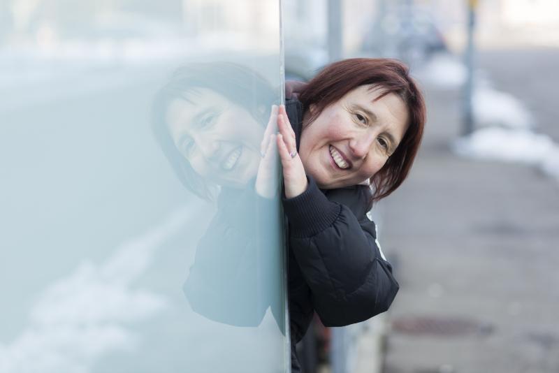 Une femme est penchée sur une vitre de verre et s'y reflète.
