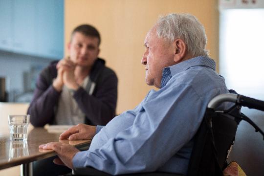 Un homme âgé en fauteuil roulant est assis ä une table et regarde au loin.