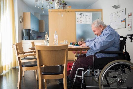 Un homme âgé en fauteuil roulant dessine à une table.