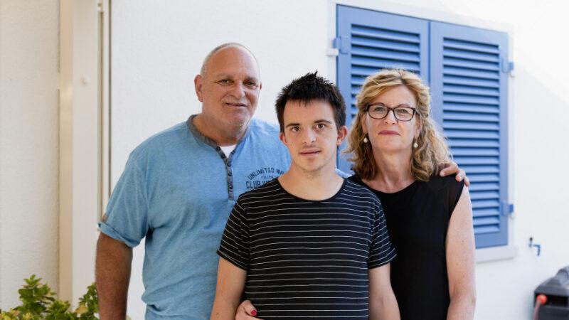 Un jeune homme et ses deux parents se tiennent debout devant une maison.