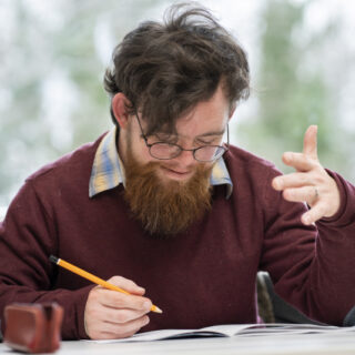 Un homme est entrain de réfléchir à un exercice écrit.