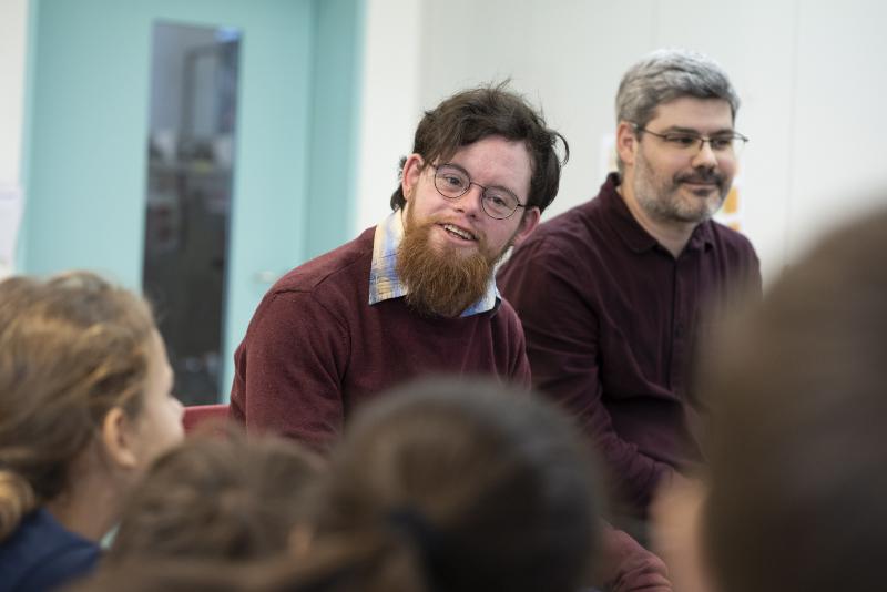 Ein junger Mann mit einer kognitiven Beeinträchtigung lächelt und spricht vor einer Gruppe von Schüler*innen.
