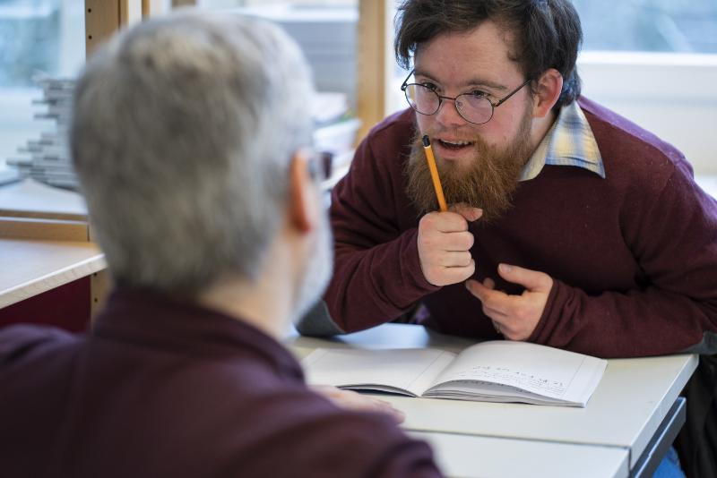 Ein junger Mann mit einer geistigen Behinderung hält einen Bleistift in der Hand und spricht mit jemandem.