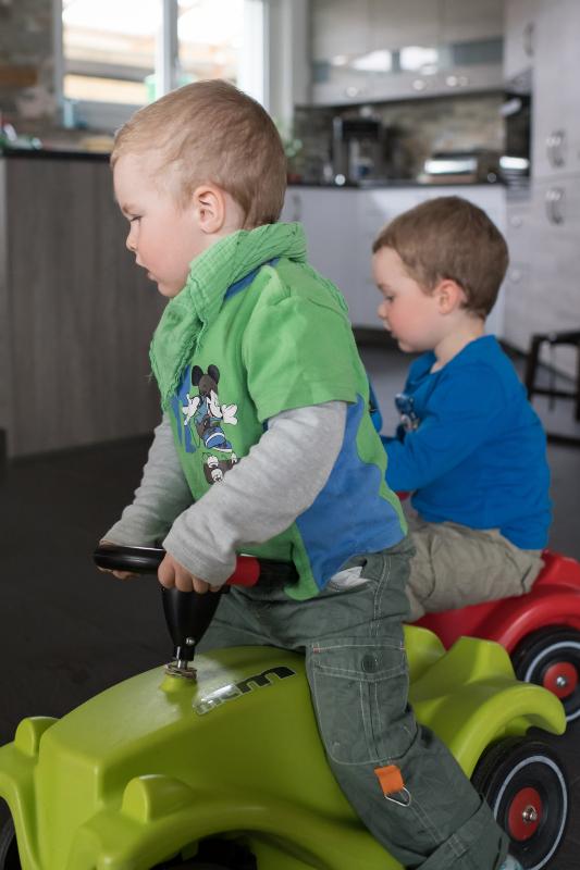 Deux enfants jouent sur leurs petits tracteurs.