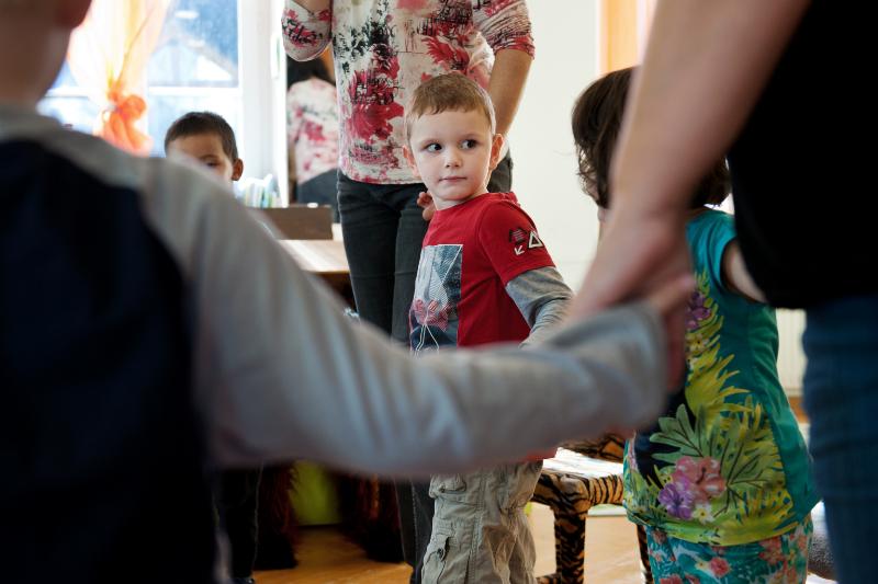 Vier Kinder und zwei Erwachsene stehen im Kreis und geben sich die Hände.
