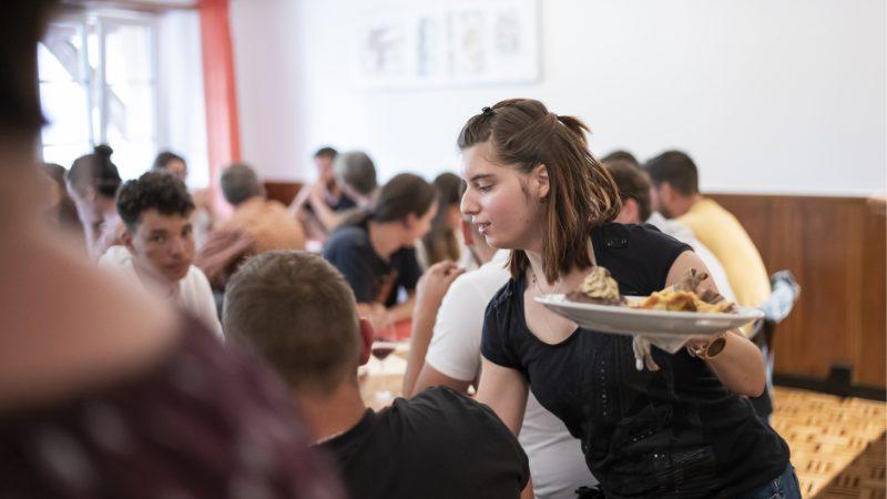 Une jeune femme est en train de servir un plat dans un restaurant.