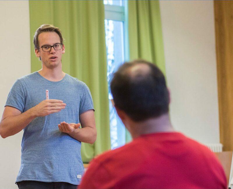 Un homme debout présente un exposé à deux personnes assises.