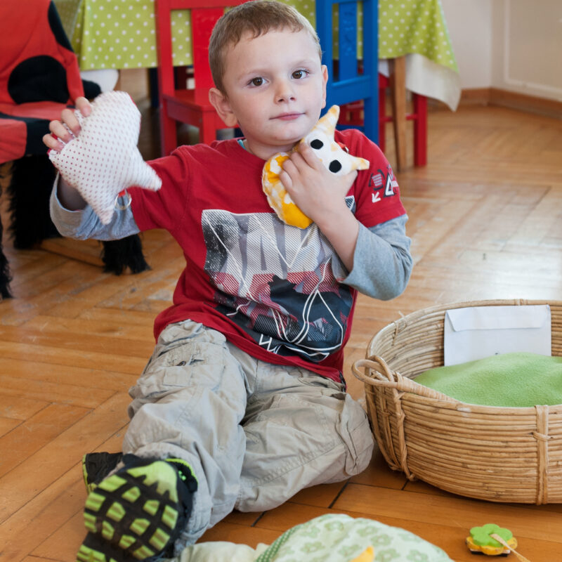 Ein junge sitzt auf dem Boden und hat zwei Plüschtiere in den Händen.