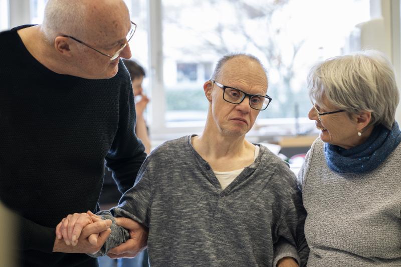 Un homme et une femme accompagnent un homme âgé et lui parlent.