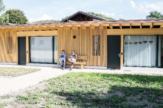 Une jeune femme et un jeune homme sont assis sur un banc devant une maison.