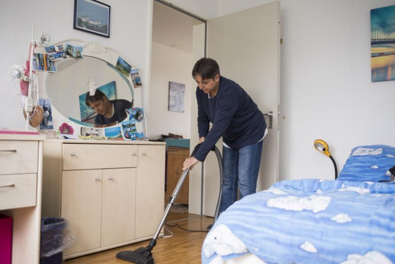 Une femme passe l'aspirateur dans sa chambre à coucher.