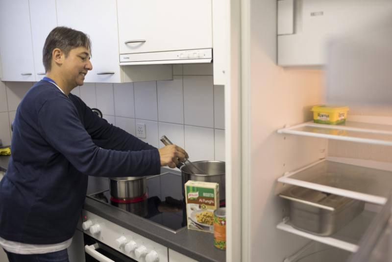 Une femme est dans sa cuisine et prépare à manger.