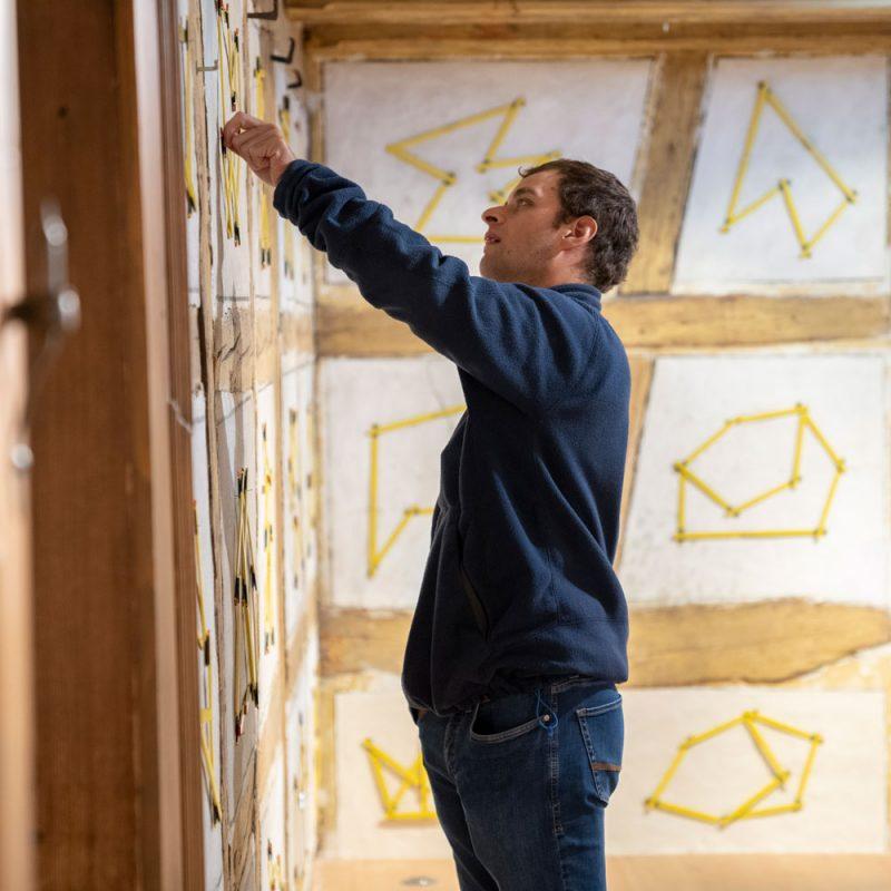Ein Mann steht vor einer Wand und zeichnet Figuren.