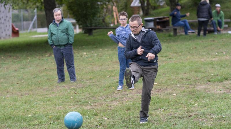 Auf einem Rasen spielt ein Junge Fussball, zwei andere schauen zu.