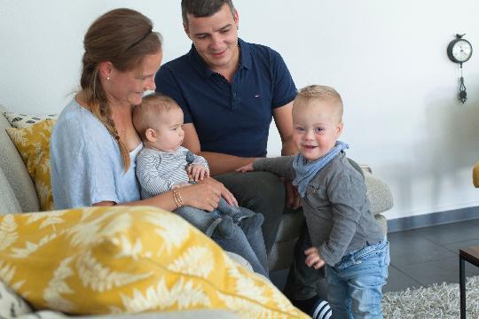 Un homme et une femme sont assis sur un canapé avec leurs deux enfants.