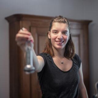 Une jeune femme tend une clé de l'hôtel dans lequel elle travaille.