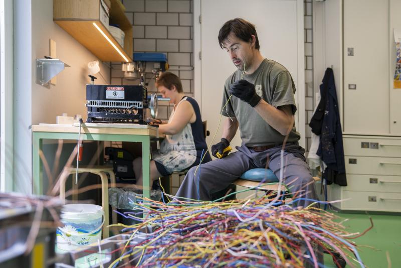 Un homme extrait le fil de cuivre de la gaine plastique d'un câble électrique.