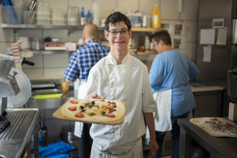 Un jeune homme sourit en présentant une flammenkuche.