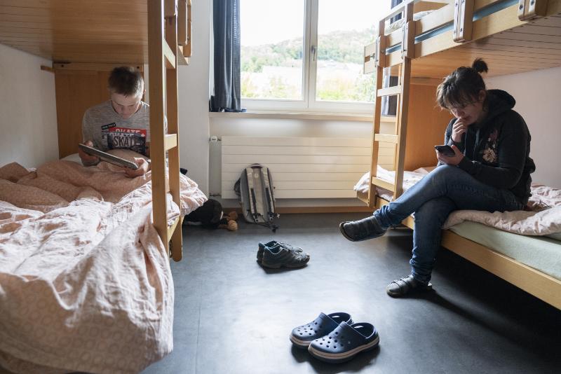 Un garçon et une fille sont assis sur des lits superposés et lisent.