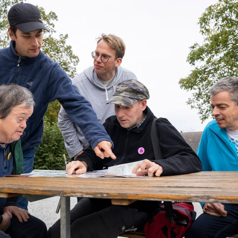 Fünf Männer sitzen und stehen um einen Tisch herum und schauen einen Prospekt an.